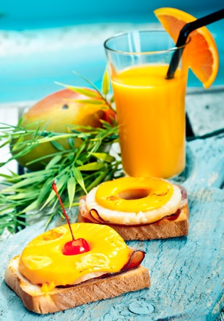 Kleurrijke tropische gezonde lunch van open ham en ananas broodjes belegd met gesmolten kaas vergezeld van verse mango juice Stockfoto