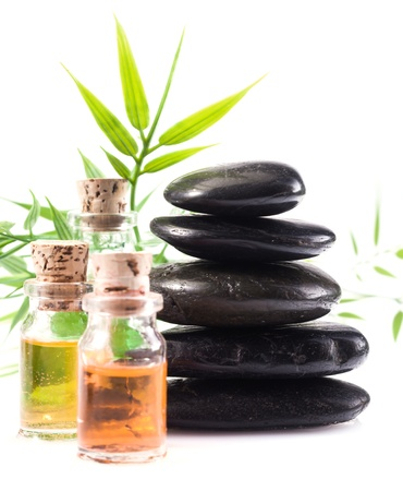 Massage oils and basalt stones necessary for a hot rock treatment in a spa setting Stock Photo