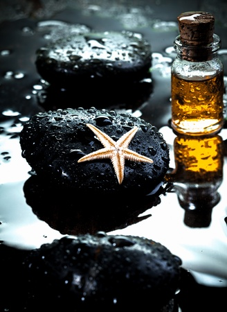 recreate: Starfish laying on a basalt stone and massage oils covered with water drops