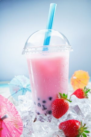 pearl tea: Fruity Strawberry Boba Bubble Tea on crushed ice, standing on a deck near the beach