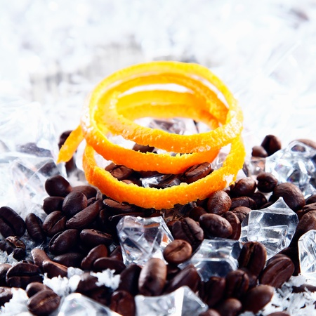 brew: Close up shot of coffe beans with ice and orange peel