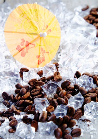 brew: Close up shot of coffee beans and ice cubes with yellow cocktail umbrella