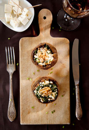 entree: Filled mushroom with cheese on wooden breadboard Stock Photo