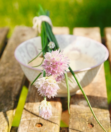Flowering Chives on old and vintage wooden Table photo
