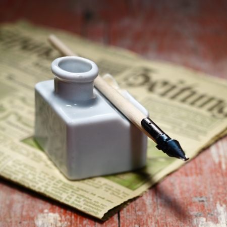 Old Ink Quill and an antique newspaper on an ancient wooden background photo