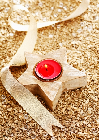 Christmas Candle with a golden bow on a festive background photo