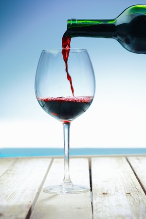 burgundy drink glass: Wine at the beach on a deck in front of the ocean Stock Photo