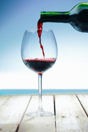 wine pouring: Wine in spiaggia su un ponte di fronte al mare Archivio Fotografico