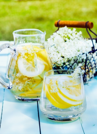 Lemon and cedar refreshment. Flowering Cedar Lemonade with water and citrus slices outdoors on a wooden table. A basket with blooming cedar in the background