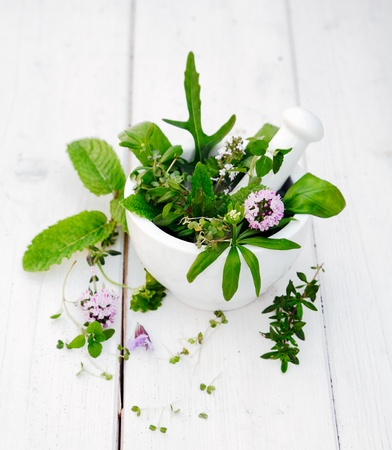 Flowering Assorted Herbs in a Mortar with pestle on white wooden background photo