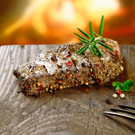 bistecche: Bistecca Rustic sulla tavola di legno di fronte al fuoco Archivio Fotografico