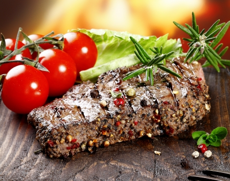 peppered: A grilled serving of succulent tender peppered steak garnished with lettuce, tomato and fresh rosemary herbs