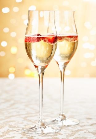 brindisi champagne: Flauti champagne di festa pieni di spumante e fragole galleggianti con un bokeh sfondo di romantiche luci scintillanti del partito