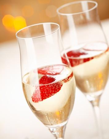 brindisi champagne: Closeup di flauti champagne alla moda pieno di frizzante refrigerata e una fragola galleggiante per celebrare una serata romantica insieme