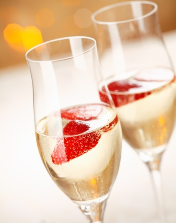 Closeup of stylish champagne flutes filled with chilled bubbly and a floating strawberry for celebrating a romantic evening together