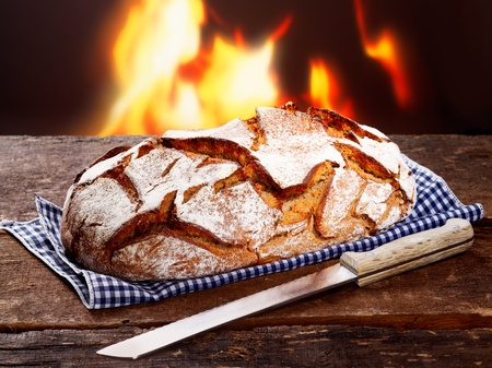 woodfired: Crisp loaf of freshly baked rye bread with a knife on a checked napkin in front of a flaming fire