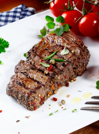 peppered: Thick portion of succulent tender peppered steak grilled to perfection and served on a plate with fresh herbs and tomatoes