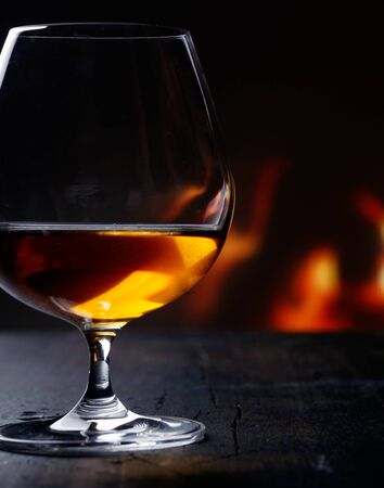 cognac: Brandy snifter warming before a glowing fire on an enjoyable and entertaining night out on the town