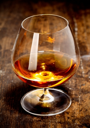 cognac: Glowing goblet of rich cognac on a wooden bar counter on a relaxing night out with friends Stock Photo