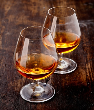 shot glass: Two goblets of brandy warmed by the glow of the lights on wooden counter top while entertaining a special friend Stock Photo