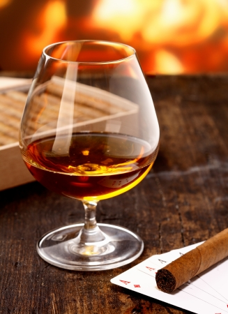 christmas debt: Goblet of cognac warming in front of the fire on a poker night with four aces and a cigar Stock Photo