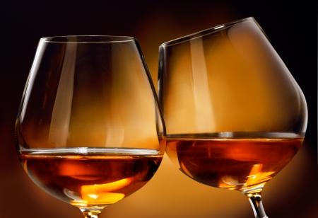 spiraglio: Per tintinnare due bicchieri di liquore Cognac o Brandy di fronte a uno sfondo marrone. Archivio Fotografico