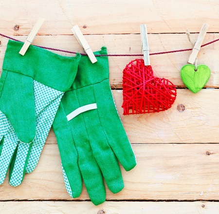 Gardening Hand Gloves  The beautyful feeling of gardening  Some hearts and gardening hand gloves on a wooden background  Square Format  For more see my portofolio Stockfoto