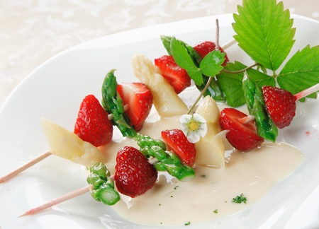alternating: Skewers with alternating fresh asparagus tips and sliced ripe red strawberries served on a plate