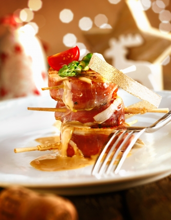 Festive medallions of pork wrapped in bacon on a dish with a beautiful boketh background photo