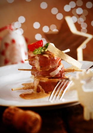 christmas food: Festive Banquet Meal. Delicious Menu served on a white plate. Tenderloin staple wrapped in bacon with a yummy sauce. Christmas decoration in the background