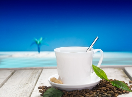 stimulant: Freshly brewed cup of coffee with coffee beans on a wooden deck overlooking the tropical ocean