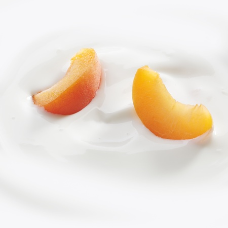 the peach: Fresh cut peach slices lay lightly on a fresh serving of yogurt