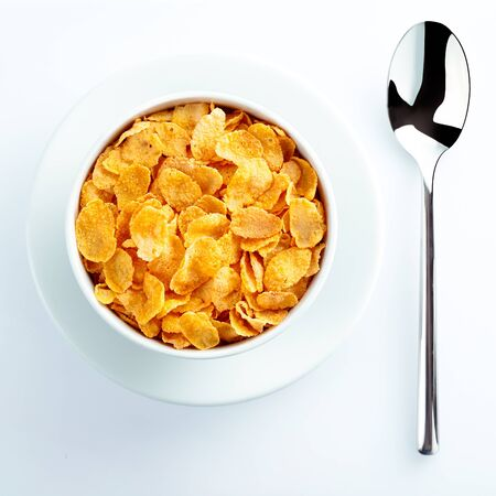 corn flakes: Bowl of cereal and spoon waiting for milk set on the table for a nutritious breakfast