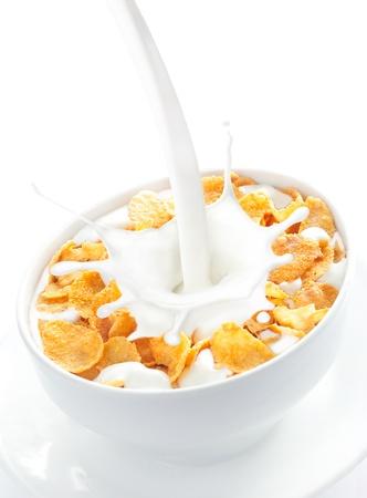 Apetitosa vista de la leche se vierte en un tazón de copos de cereal de maíz nutritivo y delicioso