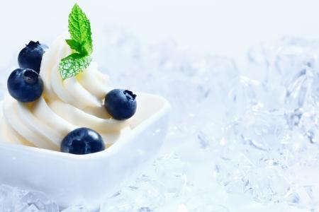 ice crushed: Blueberry bevroren yoghurt met een kopie ruimte met ijsblokjes en crushed ijs op lichtblauwe achtergrond