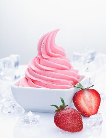 ice crushed: Bevroren aardbeien yoghurt met met vers fruit en op smaak gebracht romige yoghurt met een ijs-blokjes op een witte achtergrond Stockfoto