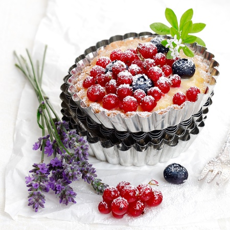 fluted: Scrumptious freshly baked red currant and blueberry tart in a decorative fluted metal pie pan with a bunch of fresh lavender Stock Photo