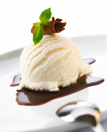 cream: Serving of ice cream and hot chocolate sauce garnished with shaved chocolate and mint