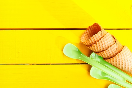 Ice cream cones and green plastic spoons on yellow table with copy space