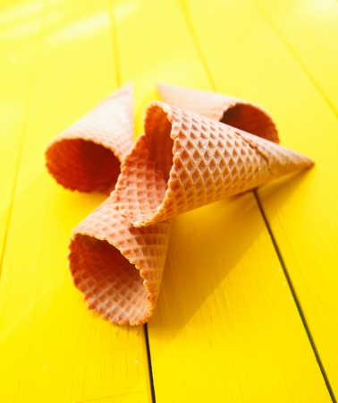 Close up shot of four Ice cream cones on yellow table photo