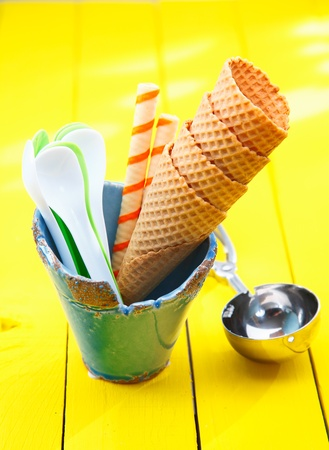 Catering still life with stacked sugar wafer icecream cones and spoons in a pottery container alongside a metal icecream scoop photo