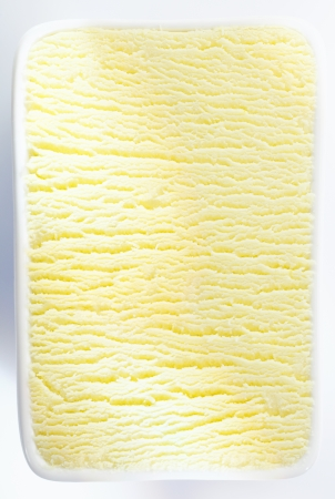 ice surface: Closeup vertical background texture of a tub of lemon sorbet or vanilla icecream with a shadowed ripple running through the centre Stock Photo