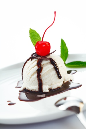 Delicious ice cream ball topped with chocolate and fresh cherry photo