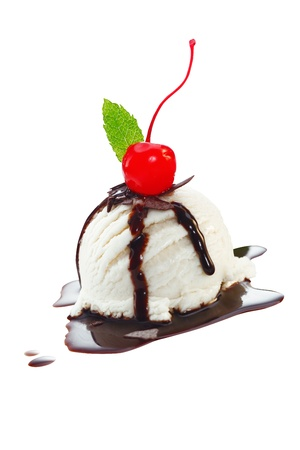 Serving of vanilla icecream with topping of melted hot chocolate sauce and a red cherry isolated on white photo