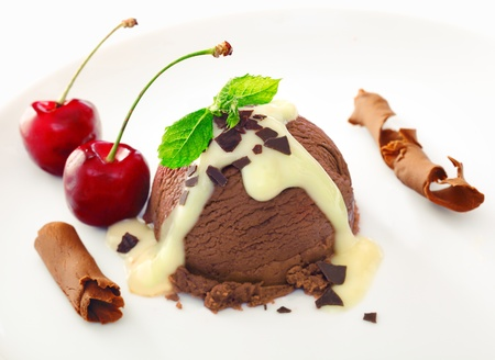 Delicious rich chocolate icecream dessert drizzled with sauce and served with ripe red cherries and coiled shavings of milk chocolate photo