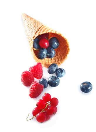Different summer fruits in an ice cream cone or wafer on white background photo
