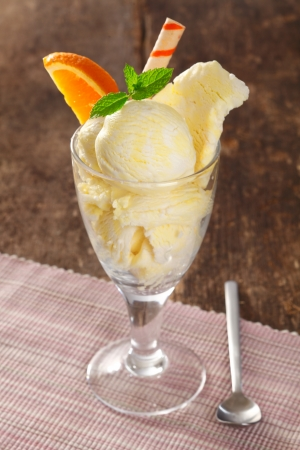 Cold creamy vanilla icecream in a tall glass garnished with mint and orange and a spiral wafer photo