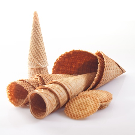 Assortment of icecream cones and cornets in different shapes and sizes together with wafer biscuits on a white background photo