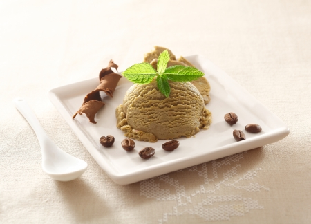 Serving of cool refreshing coffee ice-cream garnished with mint and chocolate and a scattering of roasted coffee beans photo