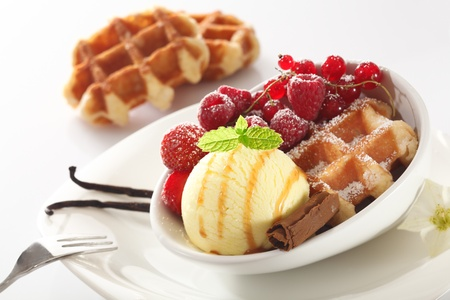 tilted view: Tilted angle view of a healthy berry and icecream dessert with raspberries, strawberries and redcurrants on a crisp baked waffle Stock Photo